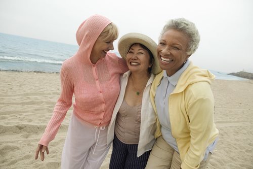 middle aged women laughing and walking on the beach