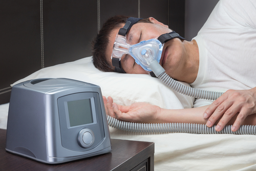 man sleeping with CPAP mask on